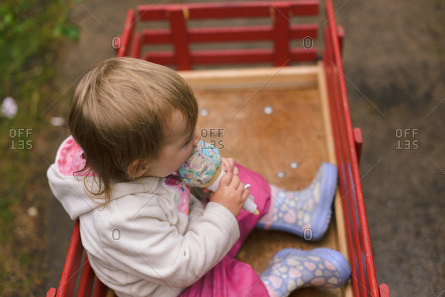 Girl in a wagon eating ice cream cone