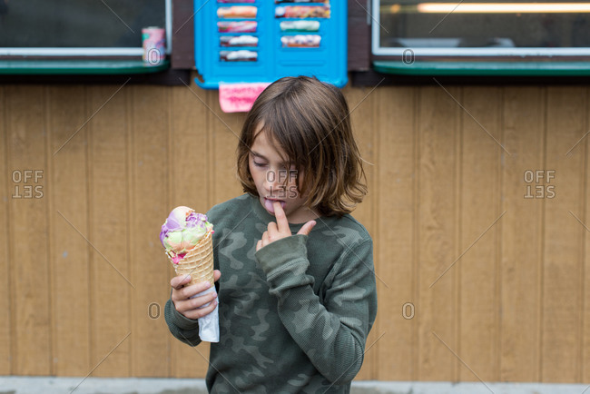 Boy eating ice cream cone by a stand