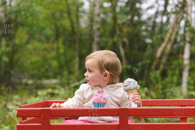 Girl in a wagon with an ice cream cone