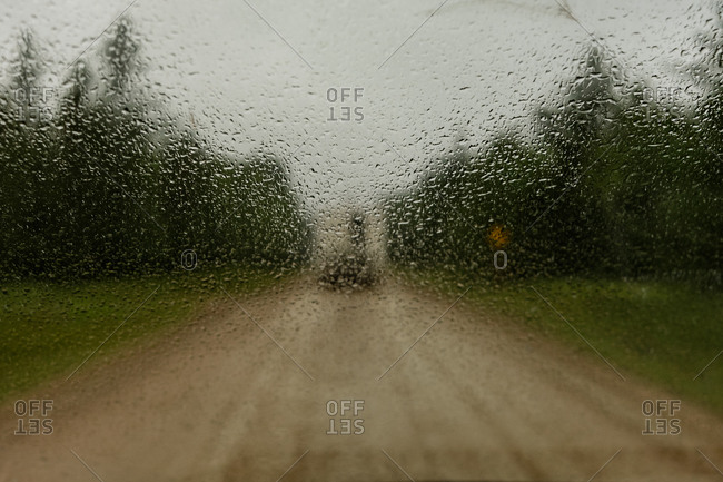 Rural dirt road seen through rainy windshield