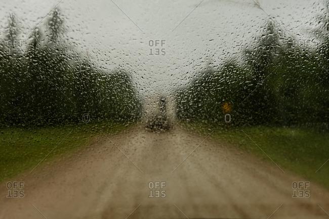 Rural dirt road seen through rainy windshield