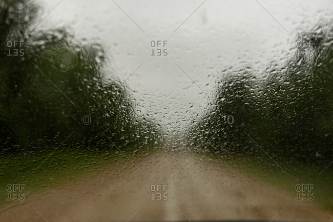Rural dirt road seen through rainy window