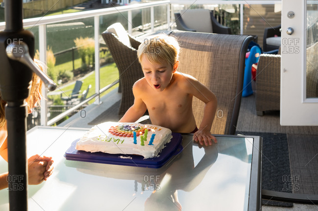 Boys on a porch blowing out birthday cake