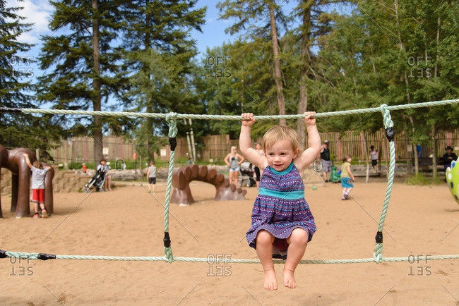 Little girl hanging from rope in a playground