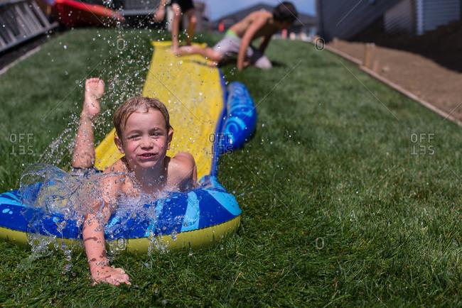 Boy sliding down plastic sheet in yard