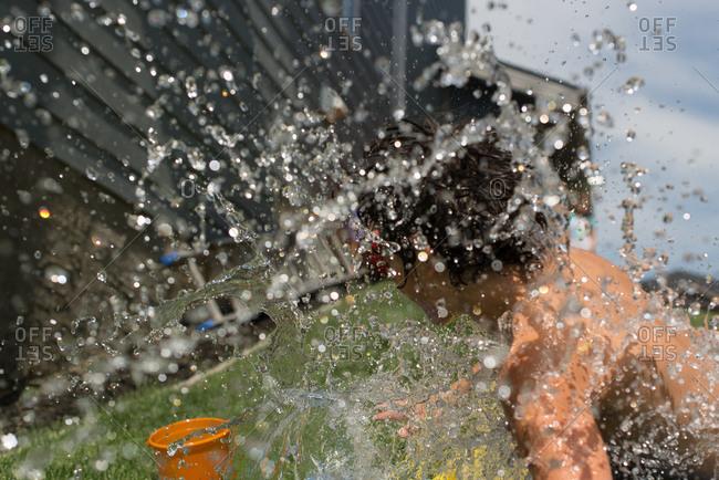 Boy splashing at bottom of water slide sheet