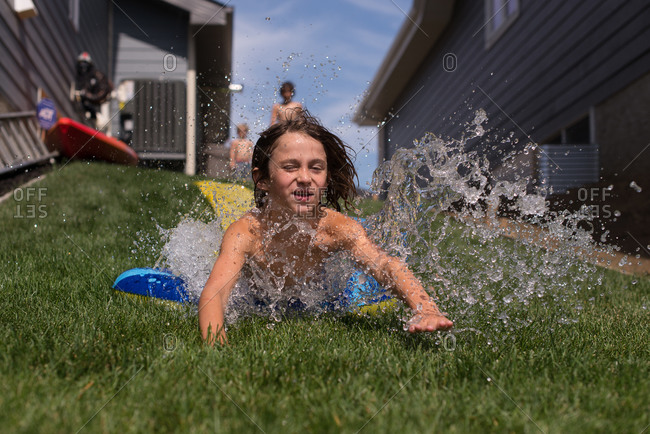 Boy going down a water slide toy