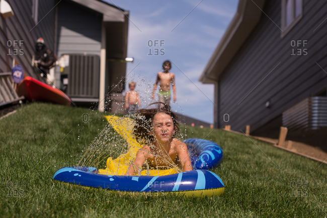 Kids playing on a plastic water slide sheet