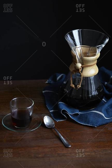 Elevated view of a Chemex coffee maker and cup of black coffee