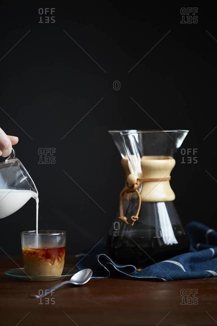 Hand pouring cream from a pitcher into cup of coffee
