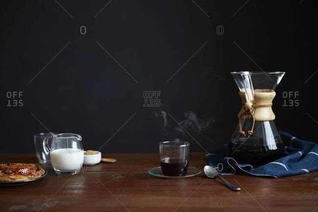Table set with a Chemex coffee maker, cup, milk, sugar and pastry