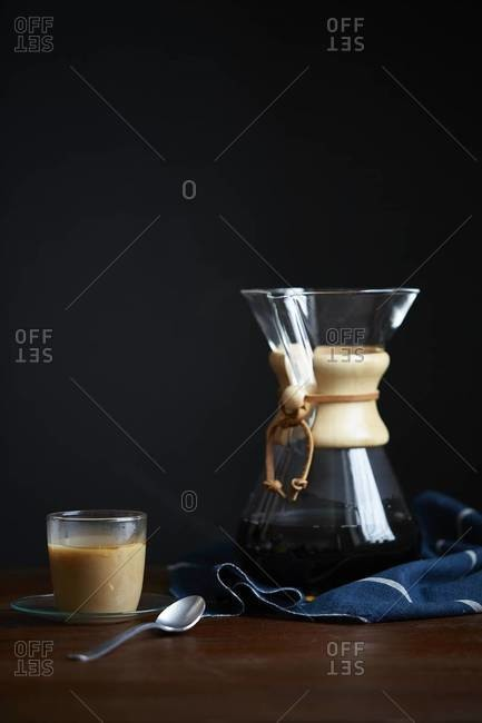Cup of coffee with cream next to a Chemex