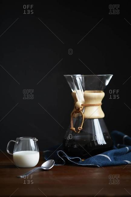 Still life of a Chemex coffee maker with pitcher of cream