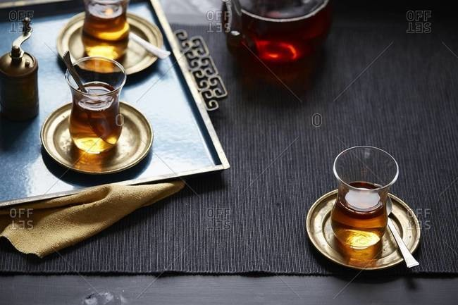 Tea tray with cups of tea and glass teapot