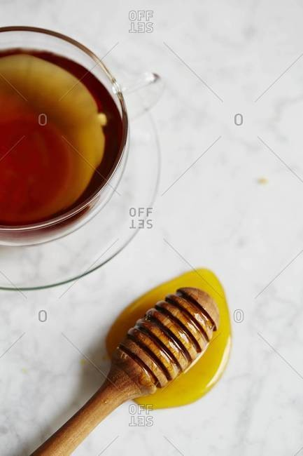 Overhead view of cup of tea and honey dipper