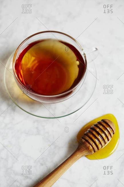 Cup of tea and honey dipper on white marble counter