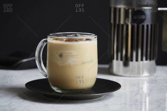 Glass mug of iced coffee with cream and French press coffee maker
