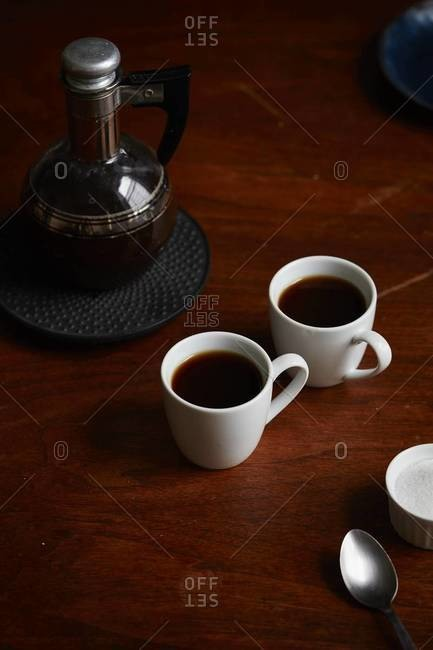 Mugs of coffee on table with narrow neck glass coffee pot