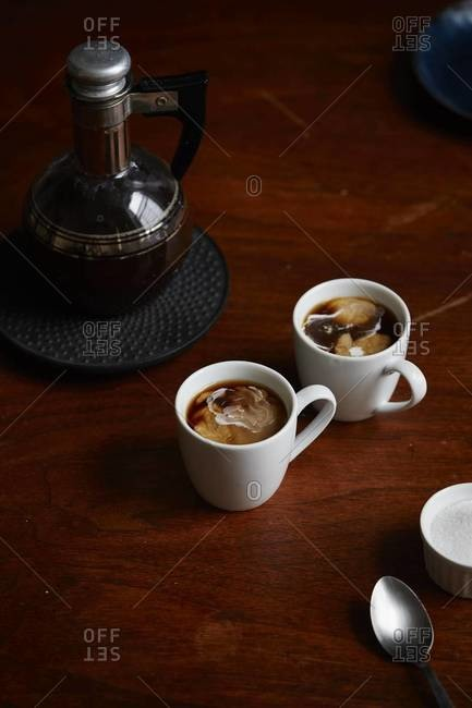 Mugs of coffee with cream on table with narrow neck glass coffee pot