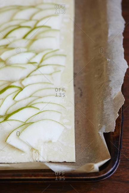 Pears slices arranged on puff pastry on parchment lined baking sheet