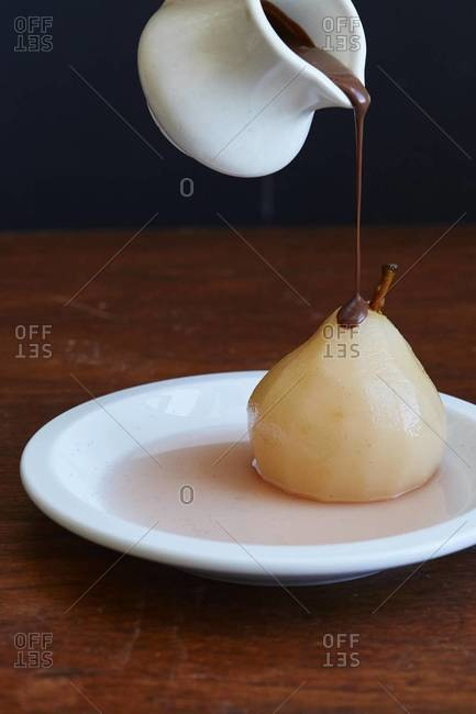 Pouring chocolate on a poached pear