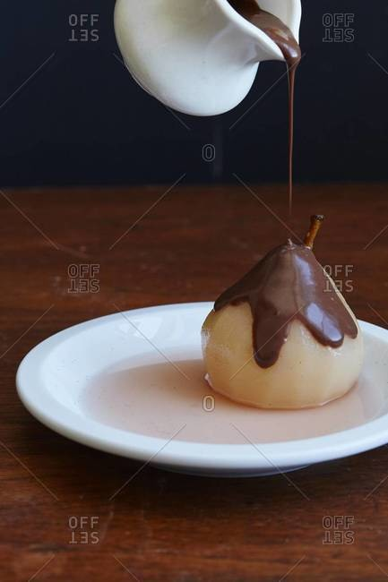 Chocolate sauce being poured over poached pear
