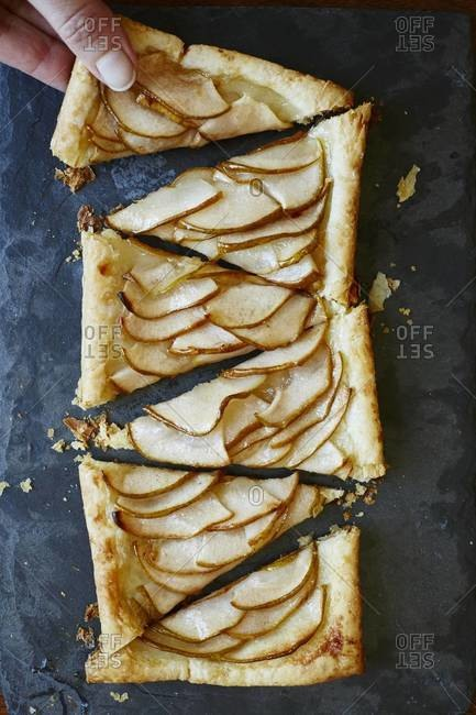 Hand taking a slice of pear tart