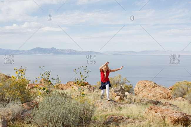 Young girl running on rocky island landscape