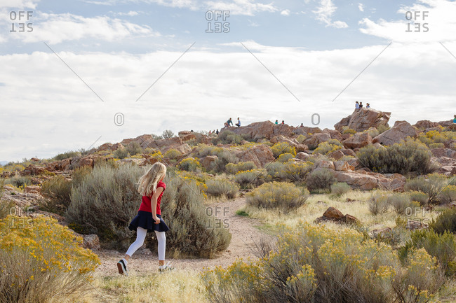 Adolescent girl walking path with other children on rocks in background