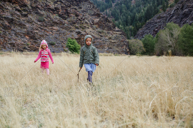 Sisters in hooded jackets exploring field of tall grass