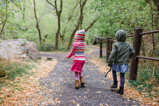 Back view of two young girls in hooded jackets walking on nature trail