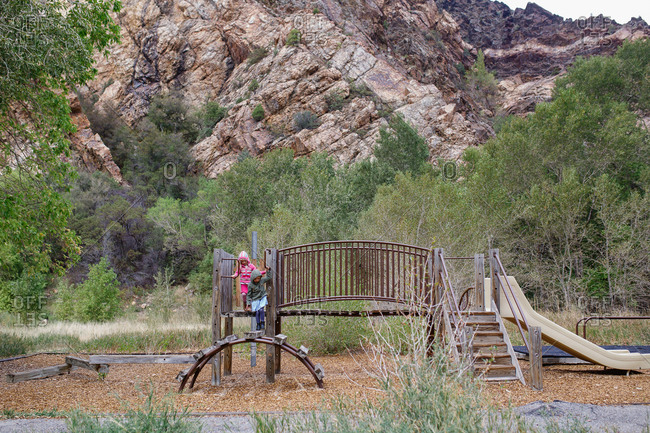 Two young girls on playground beneath rocky hills
