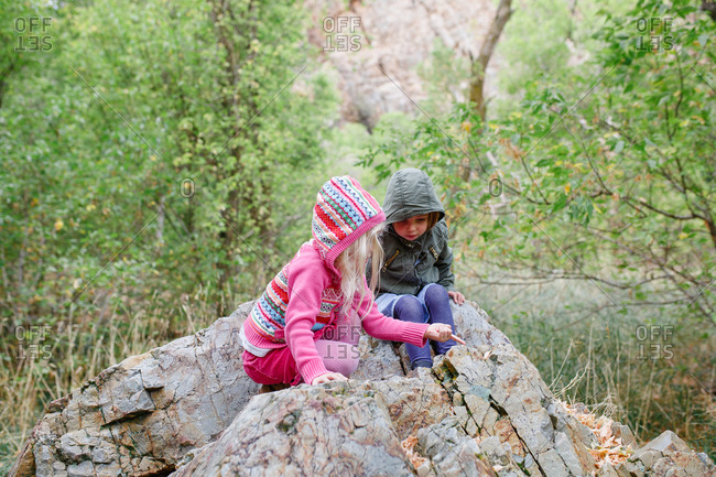 Two young sisters examining the rock they're sitting on