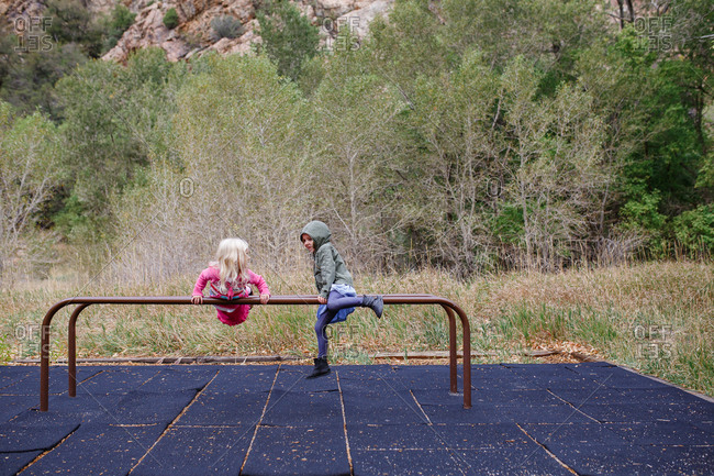 Two young girls balancing on parallel bars