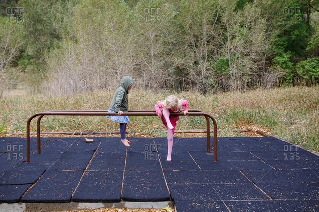 Two young girls playing on playground parallel bars