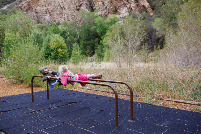 Two girl lying across parallel bars on playground