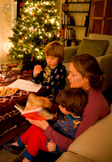 Mother reading with two boys in living room with Christmas tree