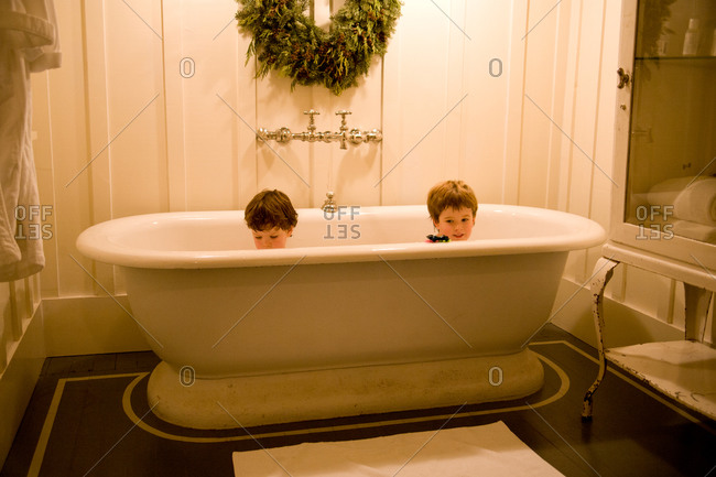 Two young boys playing in antique bathtub