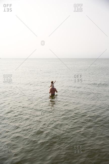 Dad giving shoulder ride to boy in sea