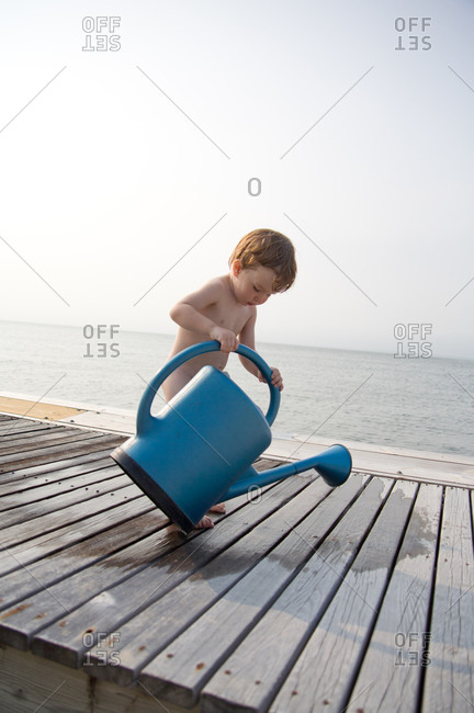Toddler boy on dock with watering can
