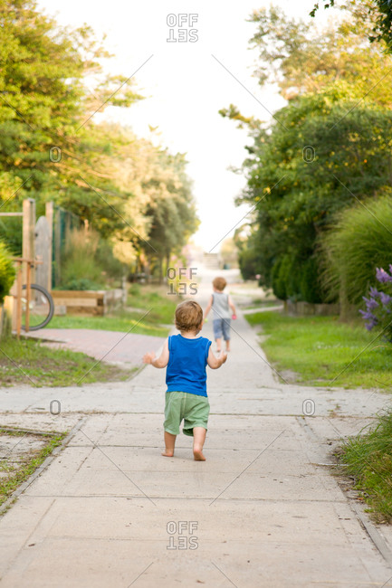Toddler boy walking down rural path alone