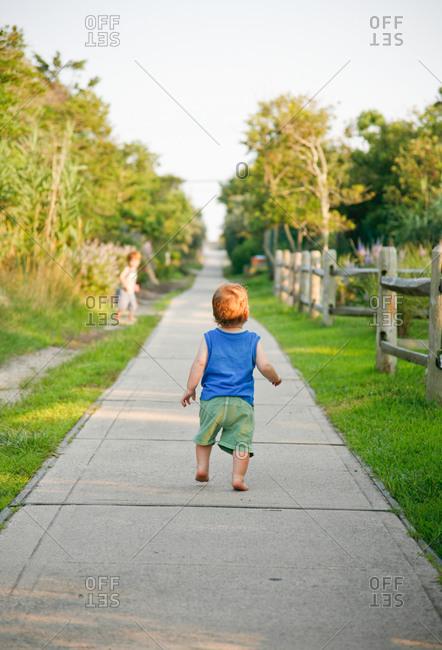 Toddler boy walking down rural pathway