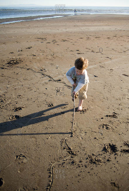 Boy drawing line in sand with a stick