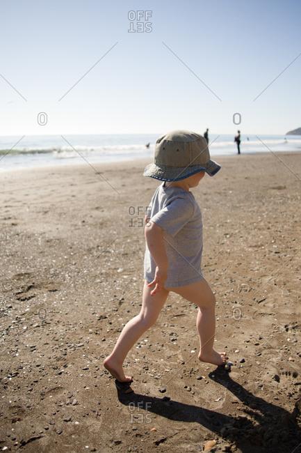 Toddler boy with no underwear walking on beach