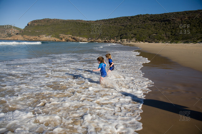 Two little boys stepping into ocean surf