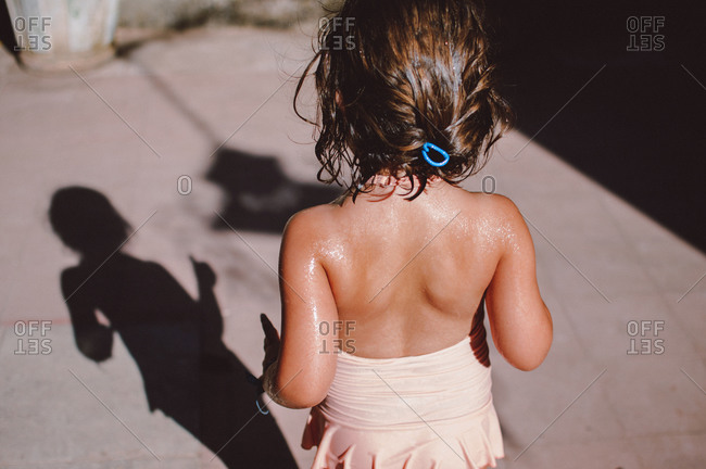 Elevated view of young girl in bathing suit and her shadow