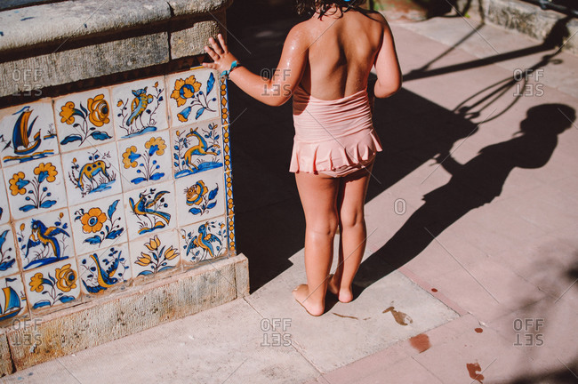 Little girl in swimsuit standing next to a tiled wall