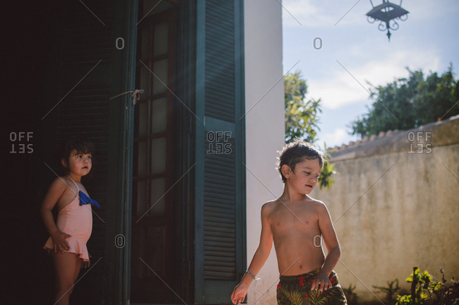 Two young children in swimsuits playing on garden patio