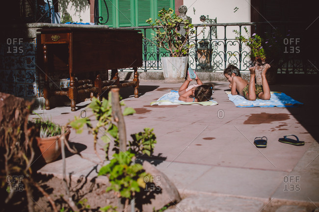 Two young children lying on towels on garden patio