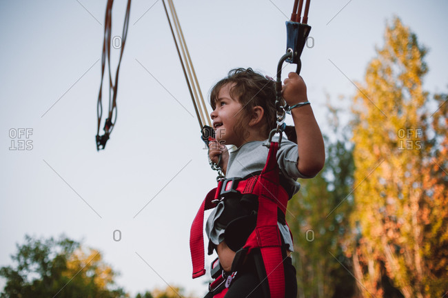 Young girl in trampoline harness